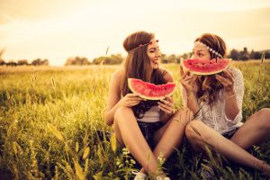 Happy hipsters in field eating watermelow